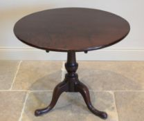 A George III mahogany tripod table, the circular tilt top raised upon a ring turned baluster