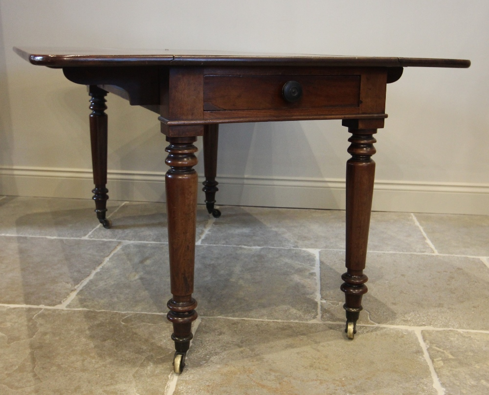 A mid 19th century Pembroke table, the rectangular drop leaf top with rounded corners, above a