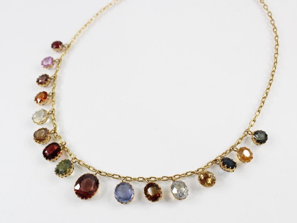 An Edwardian multi gem set fringe necklace, comprising sixteen graduated oval gemstones, including