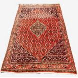 A Turkish village wool rug, with a traditional lozenge design wit extensive geometric motifs against