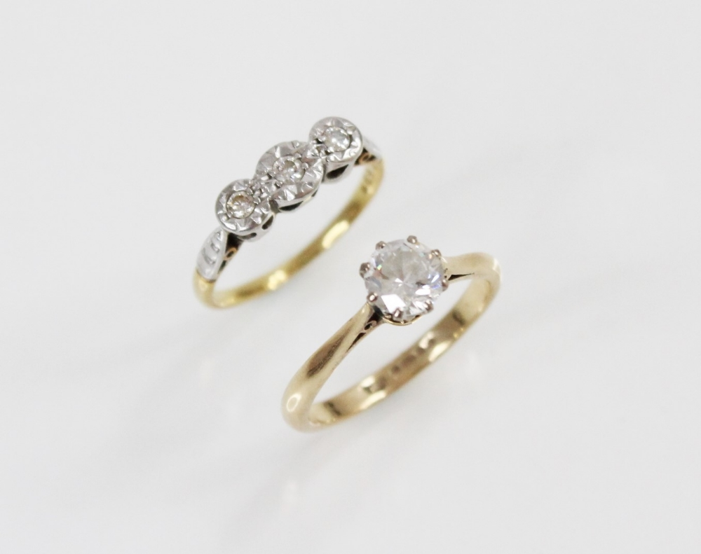 A diamond three-stone ring, comprising a central round brilliant cut diamond (weighing approximately