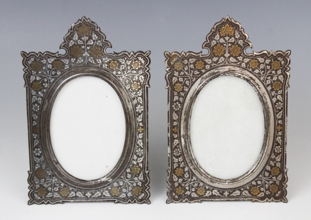 A pair of Islamic style niello gilt and white metal inlaid crested frames, extensively decorated