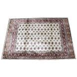 An ivory ground full pile Kashmir carpet, with an all over Bokhara design, 240cm x 160cm