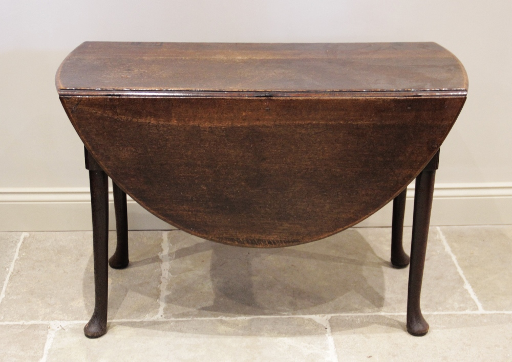 A mid 18th century oak drop leaf dining table, on tapering legs with pad feet, 70cm H x 106cm W x