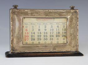A George V silver mounted desk calendar, Birmingham 1924, the rectangular aperture displaying days