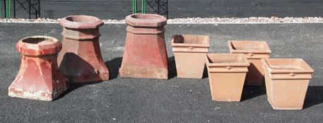 A set of four terracotta stone planters, each of tapering square form, 28cm high, along with three
