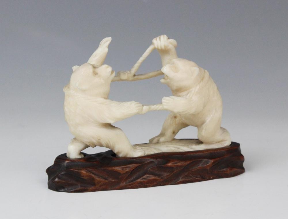 A Japanese carved ivory okimono, Meiji period (1868-1912), modelled as two battling monkeys, 9cm