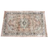 A Persian pattern silk work rug, the foliate medallion design upon a pale red ground, within a