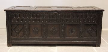 A 17th century oak coffer, the hinged cover with four invert moulded panels above a double nulled