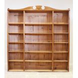 An early 20th century honey oak open bookcase, the shaped pediment with a shield shaped motif