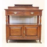 A late Victorian walnut dumb waiter, with a scrolling leaf carved pediment over two frieze