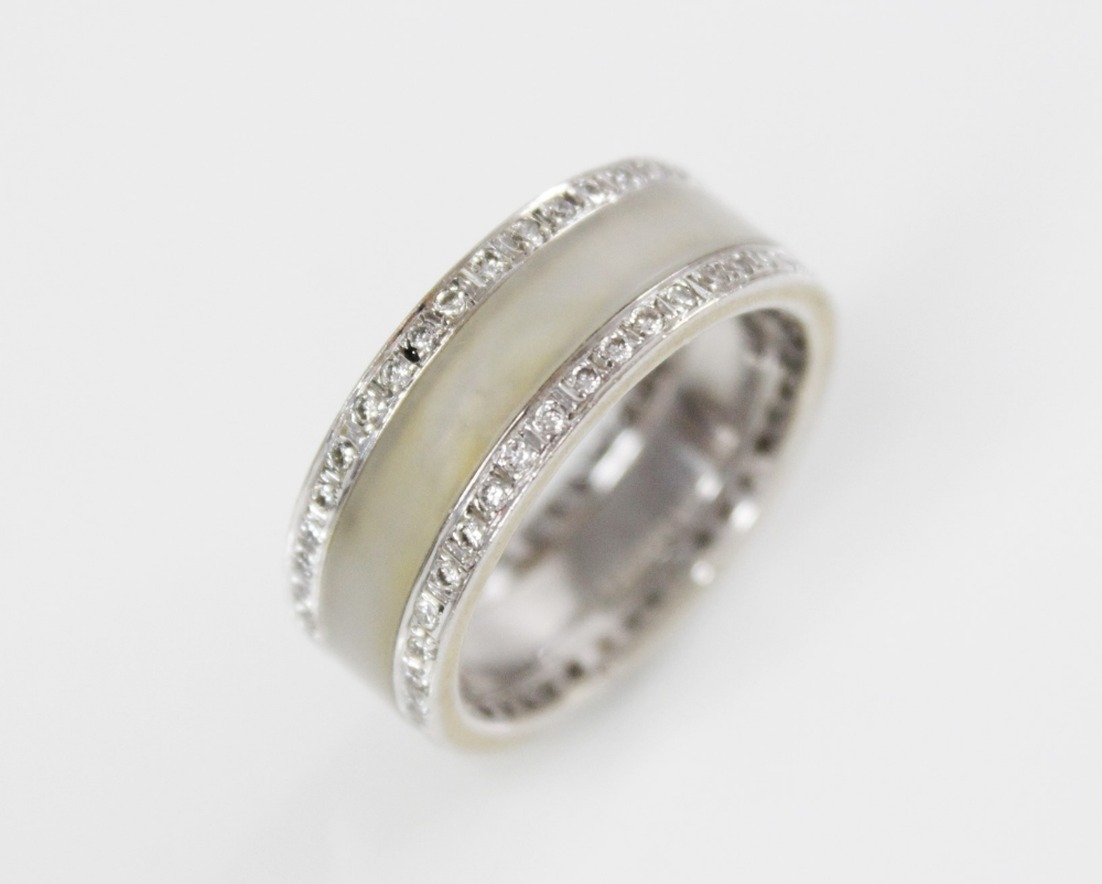 A jade and diamond 18ct white gold ring, the central channel set with polished jade, flanked by