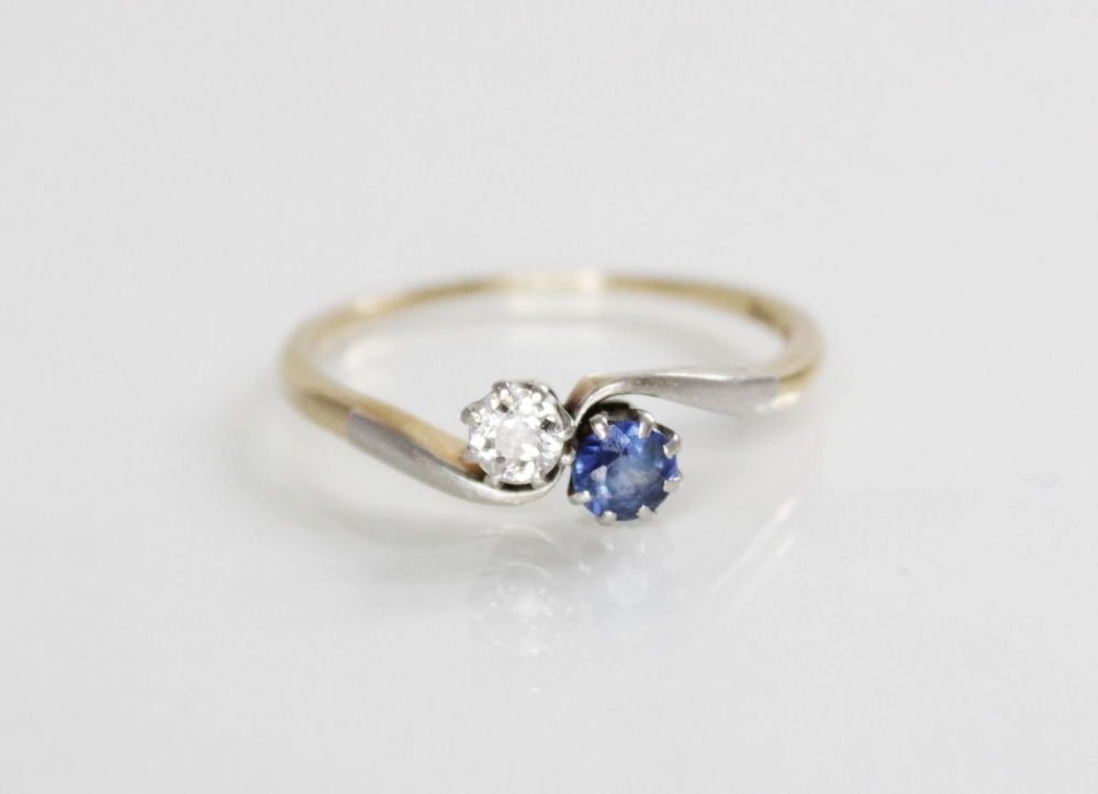 A diamond and sapphire two-stone ring, comprising a round mixed cut diamond (measuring 3.5mm