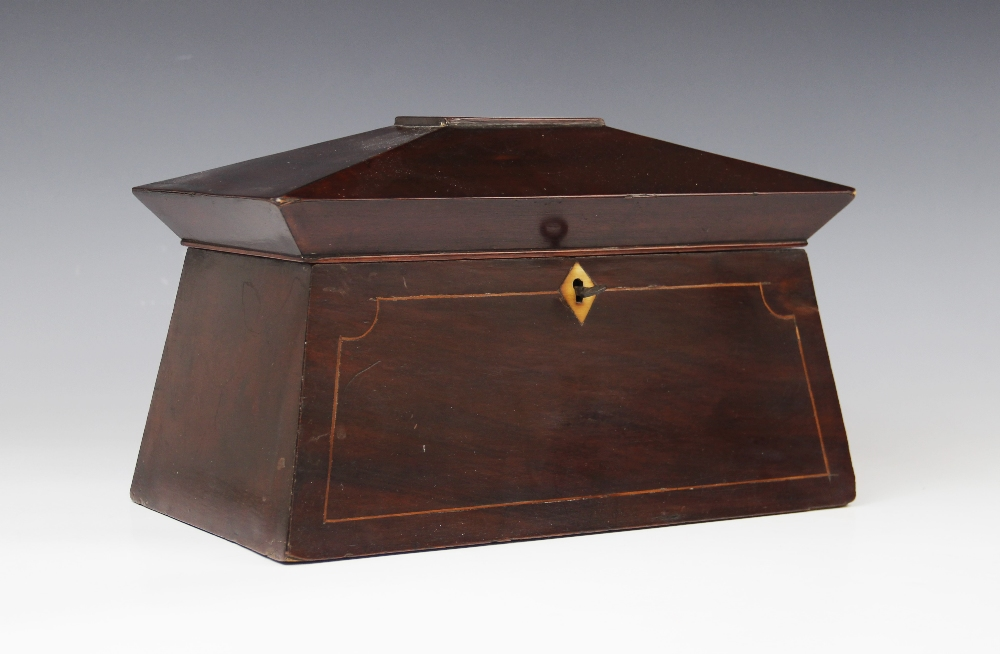 A George III mahogany tea caddy, of sarcophagus form , the pagoda shaped hinged cover centred with