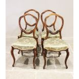 A set of six Victorian walnut dining chairs, each with a leaf swept balloon back above a stuff
