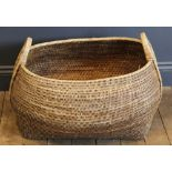 A wicker basket of large proportions, of swelling lozenge form with loop handle to each end,