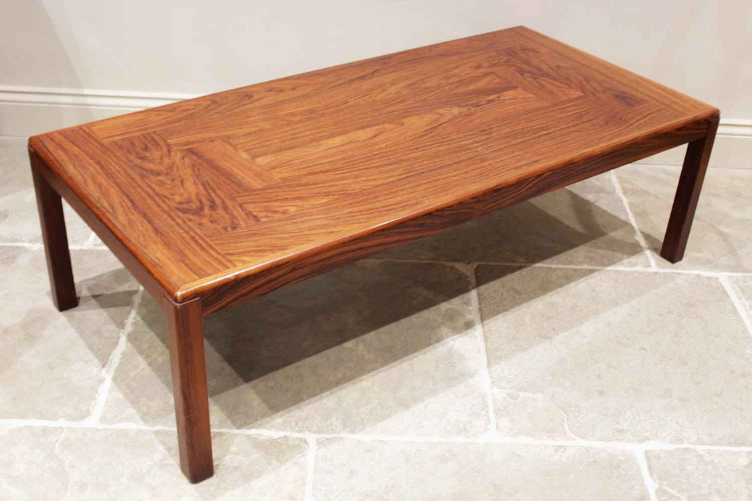 A mid century rosewood coffee table, probably Indian rosewood, the rectangular top on rounded legs