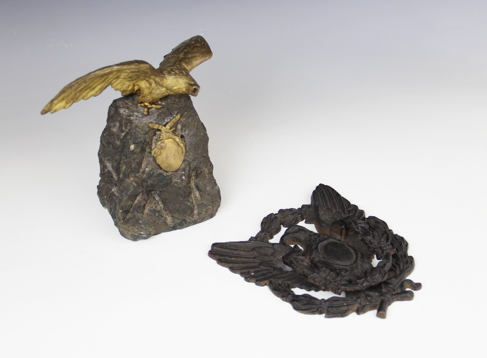 An early 20th century gilt metal figure of an eagle above a ribbon tied oval cartouche, mounted upon