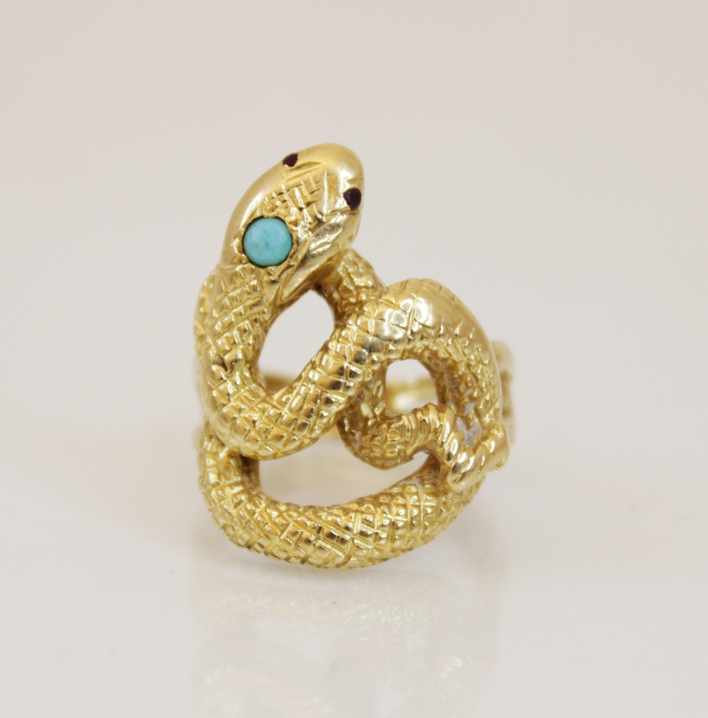 A continental 18ct gold turquoise and ruby set snake ring, the coiled body with engraved decoration,