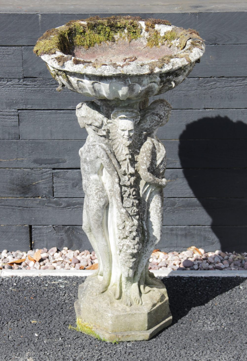 A reconstituted stone figural bird bath, the circular bowl upon an integrated 'Three muses'