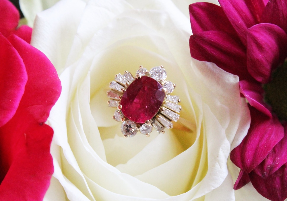 A ruby and diamond cluster ring, the central rectangular cushion cut ruby (measuring 8.2 x 6.6 x 4.