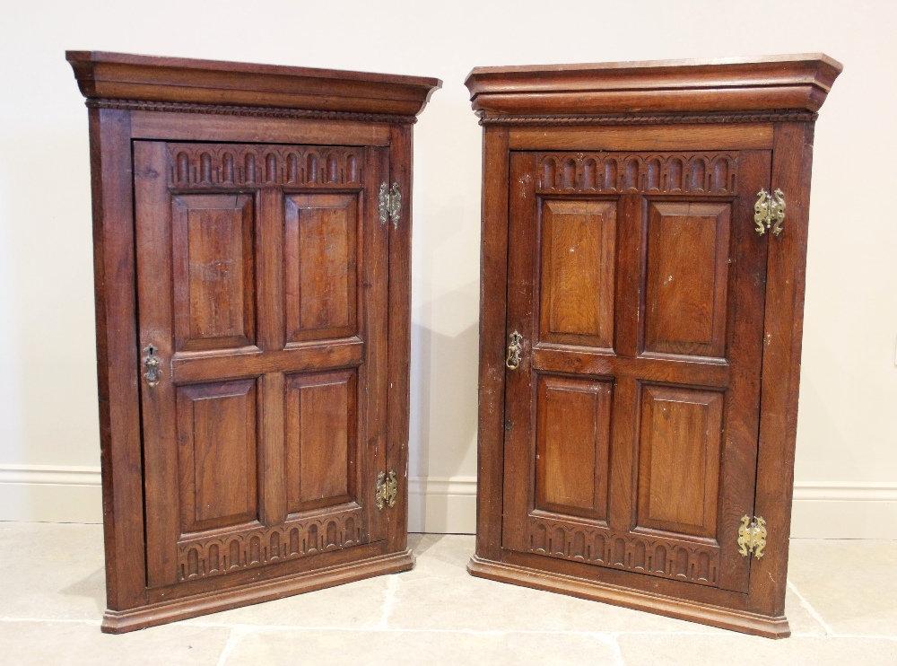 A near pair of 17th century influence oak hanging corner cupboards, each cupboard with a moulded