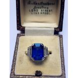 An Art Deco sapphire and diamond ring, the central octagonal step cut sapphire (measuring 11.79mm