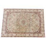 A Persian pattern silk work rug, the trailing foliate design enclosing a central flower head