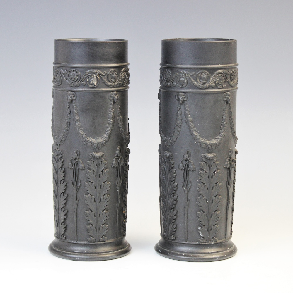 A pair of Wedgwood black basalt cylinder vases, early 20th century, the bodies extensively decorated
