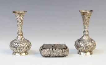 A pair of Burmese white metal posy vases, each with compressed circular bodies with tapering necks