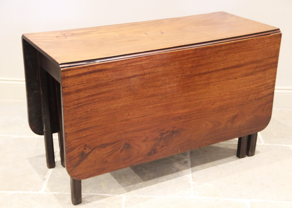 A George III mahogany drop leaf dining table, the rectangular top on channelled legs of square