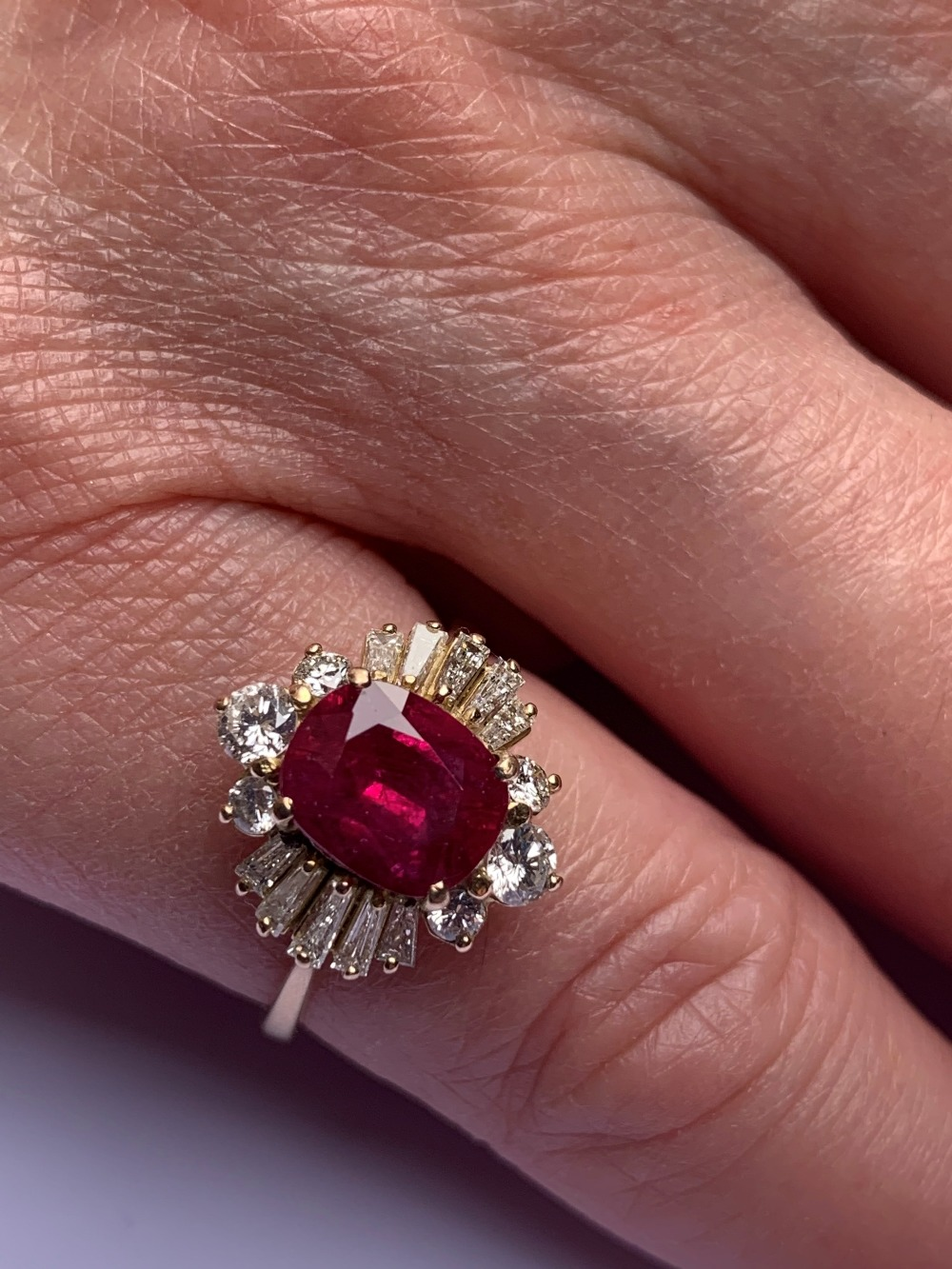 A ruby and diamond cluster ring, the central rectangular cushion cut ruby (measuring 8.2 x 6.6 x 4. - Image 8 of 10