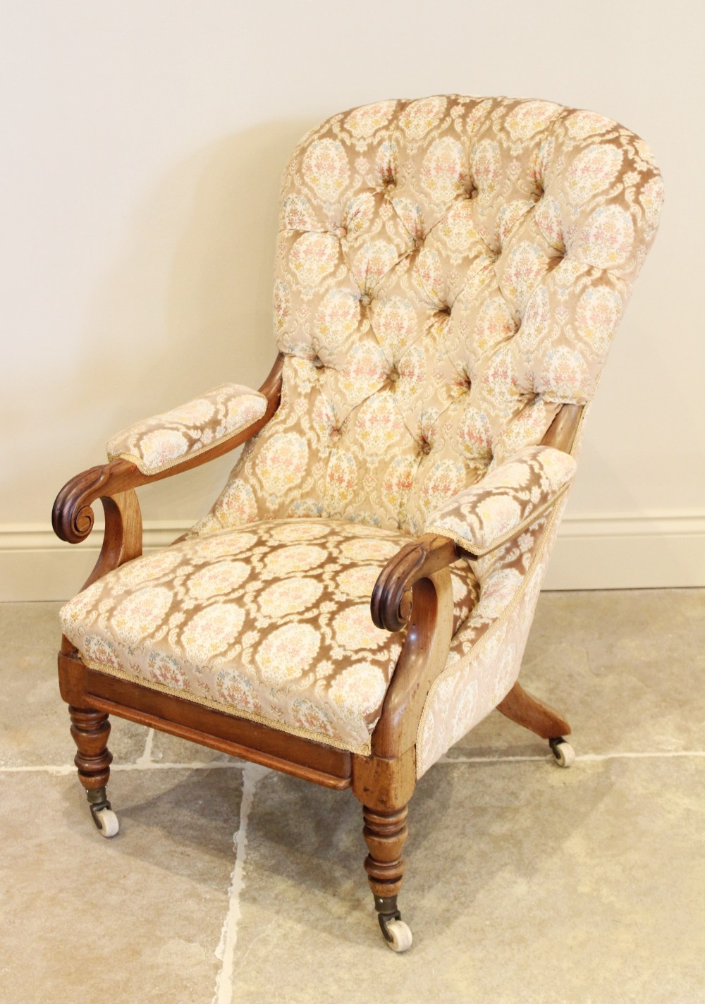 A Victorian upholstered mahogany drawing room chair, the arched button back extending to padded