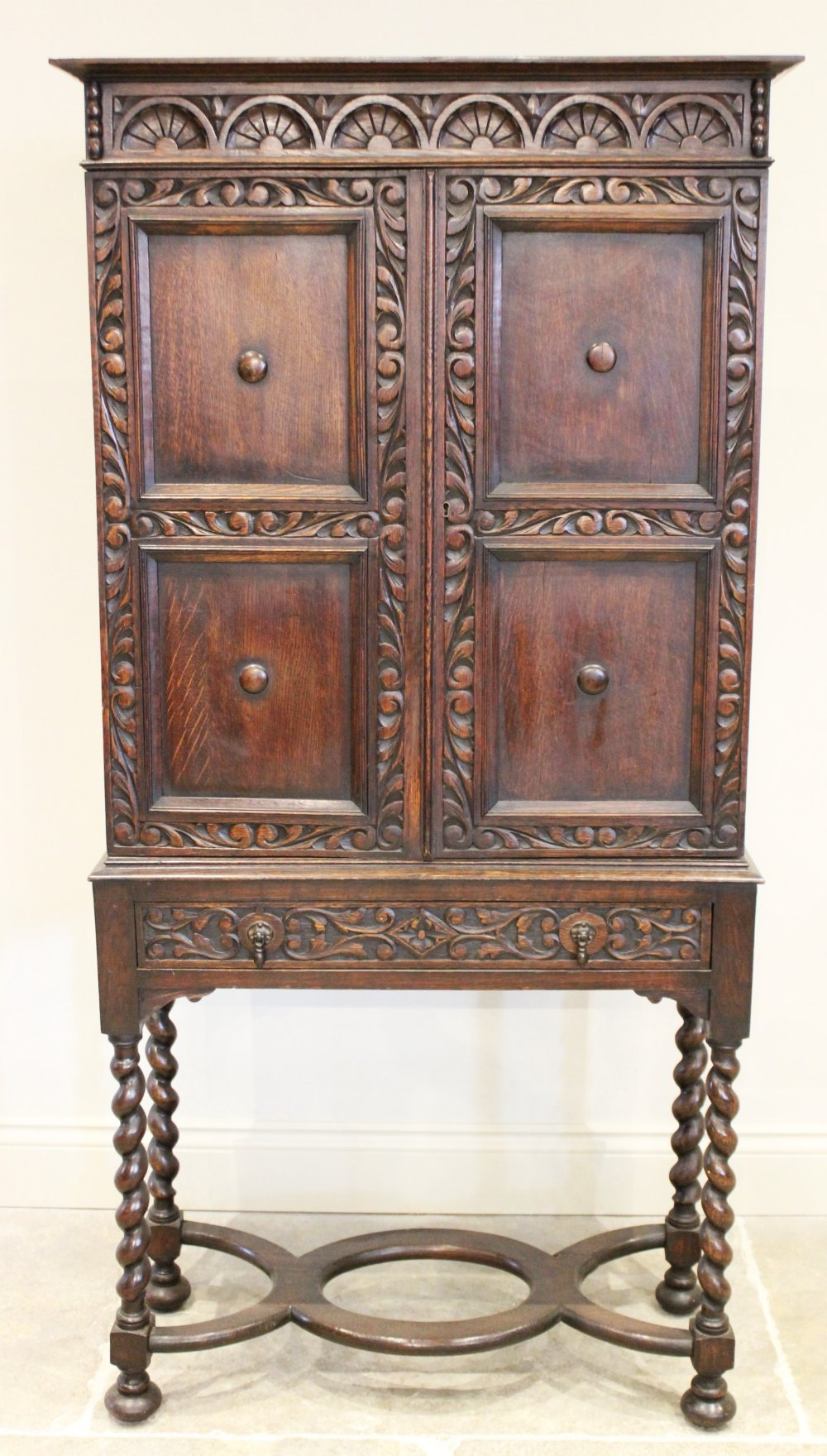 A 17th century style oak cabinet on stand, circa 1930, the lunette carved frieze above twin panelled
