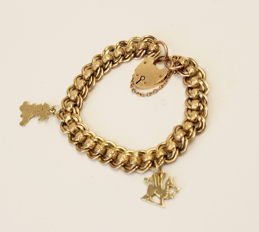 An early 20th century yellow metal charm bracelet, double curb link chain with engraved rollerball - Image 2 of 2