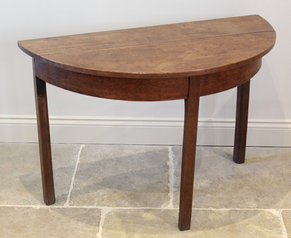 A George III honey oak D end side table, the bow front top raised upon legs of square section,