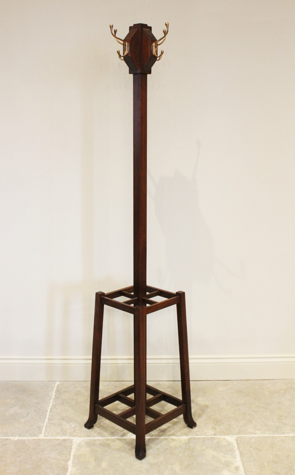 An early 20th century Arts and Crafts mahogany freestanding coat/hat stand, the four brass hooks