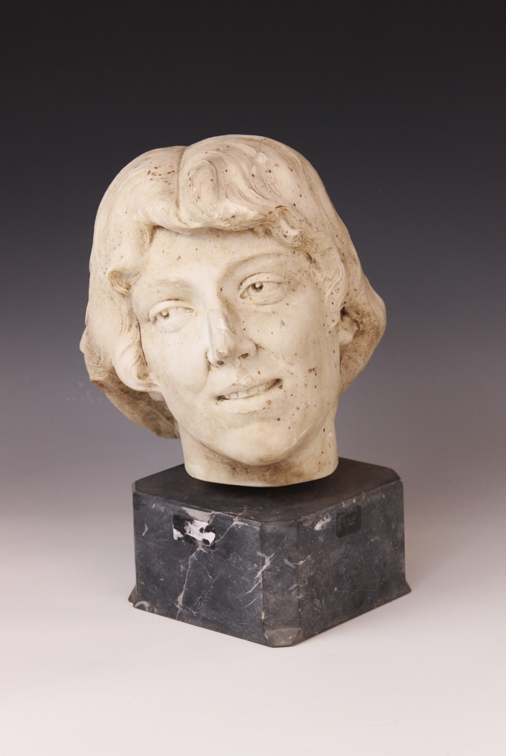 An Art Deco marble sculpture of a female head, early 20th century, set above a grey marble plinth,