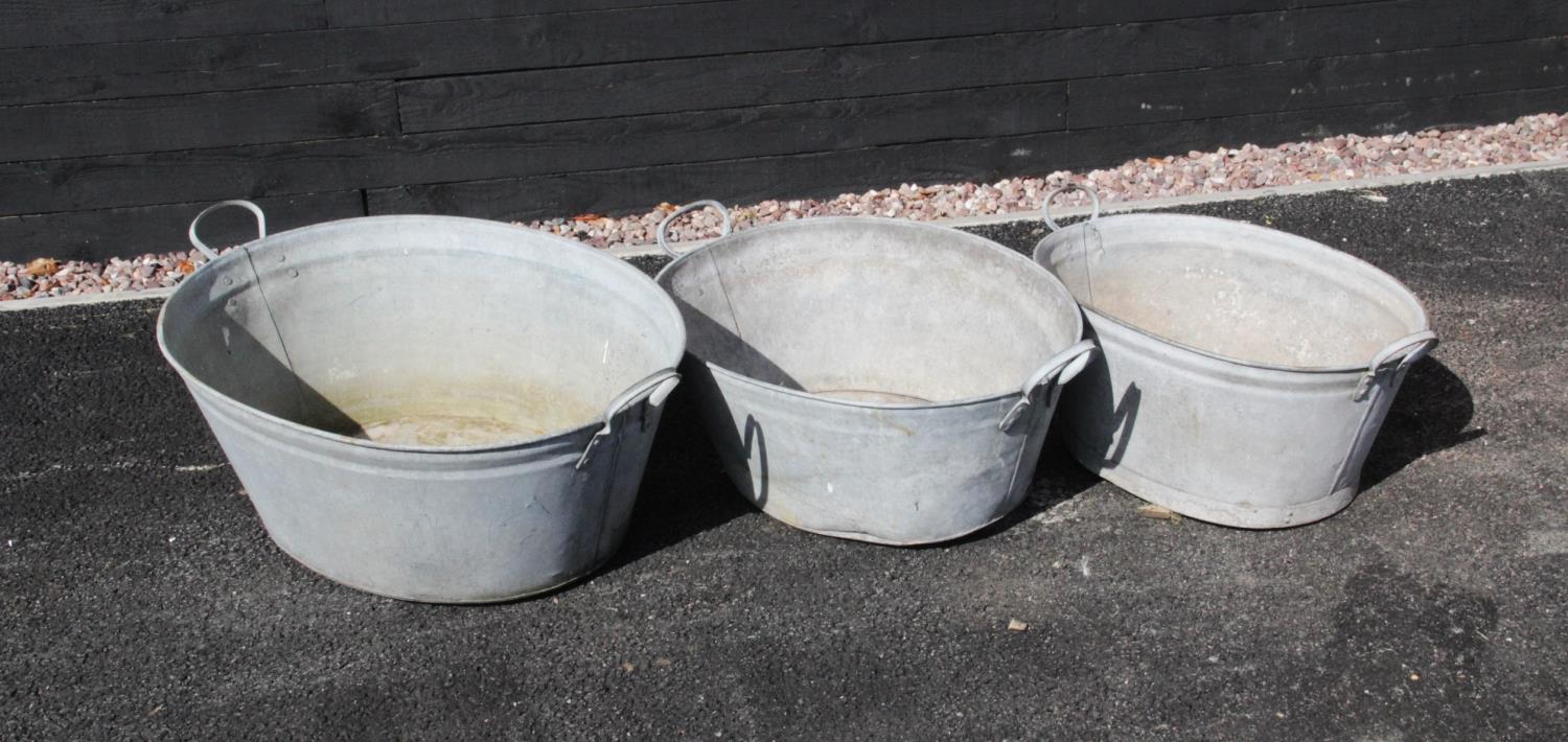Three graduated galvanised tubs, each of oval form, applied with side loop handles, the widest 86cm