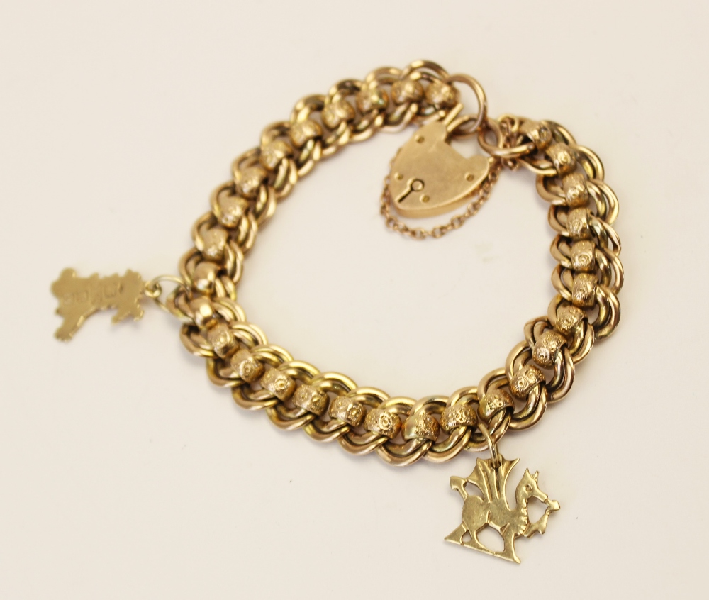 An early 20th century yellow metal charm bracelet, double curb link chain with engraved rollerball