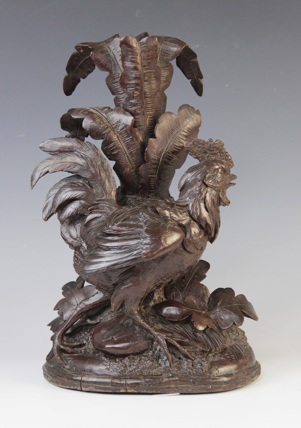 A Black Forest wood carving, probably 20th century, modelled as a cockerel strutting across a
