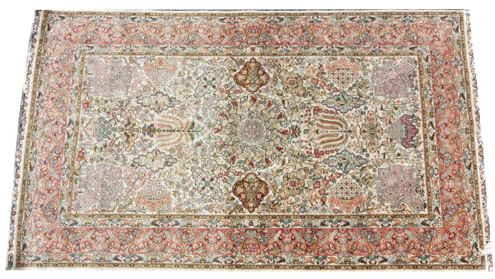 A Persian pattern silk work rug, the stylised mirrored garden design upon an ivory coloured