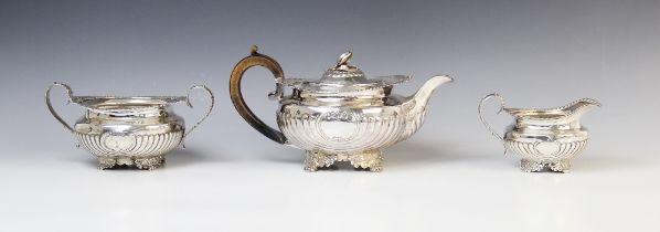 A George III silver three piece tea service by Joseph Angell I, London 1815, comprising teapot, milk