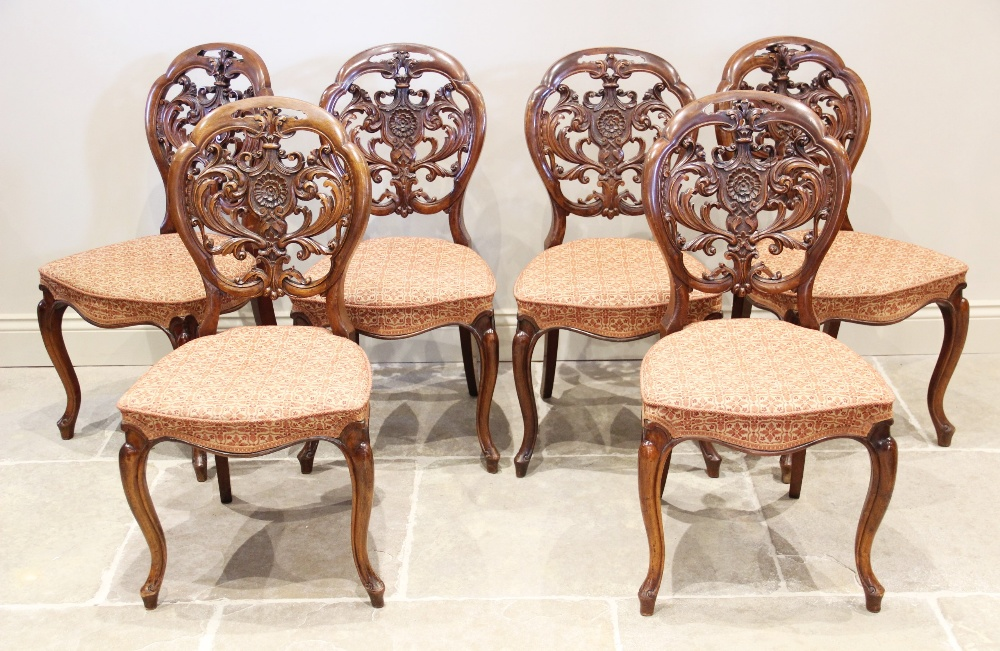 A set of six Victorian walnut balloon back dining chairs, the openwork backs carved with scrolling