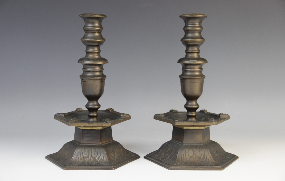 A pair of Arts and Crafts style bronze candlesticks, the hexagonal leaf cast plinth base below a
