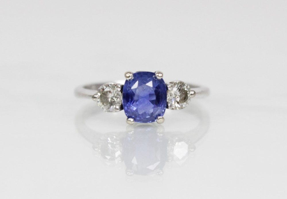 A sapphire and diamond three-stone ring, the (untested) central mixed, cushion cut sapphire ( - Image 2 of 8