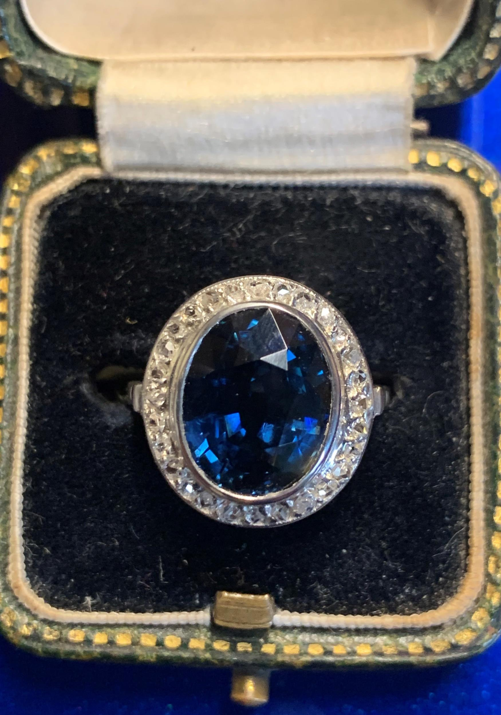 A sapphire and diamond cluster ring, the central oval mixed cut blue sapphire (measuring 12.20mm x