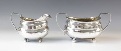 A George III silver milk jug by Solomon Hougham, London 1814, of oval bellied form with reeded