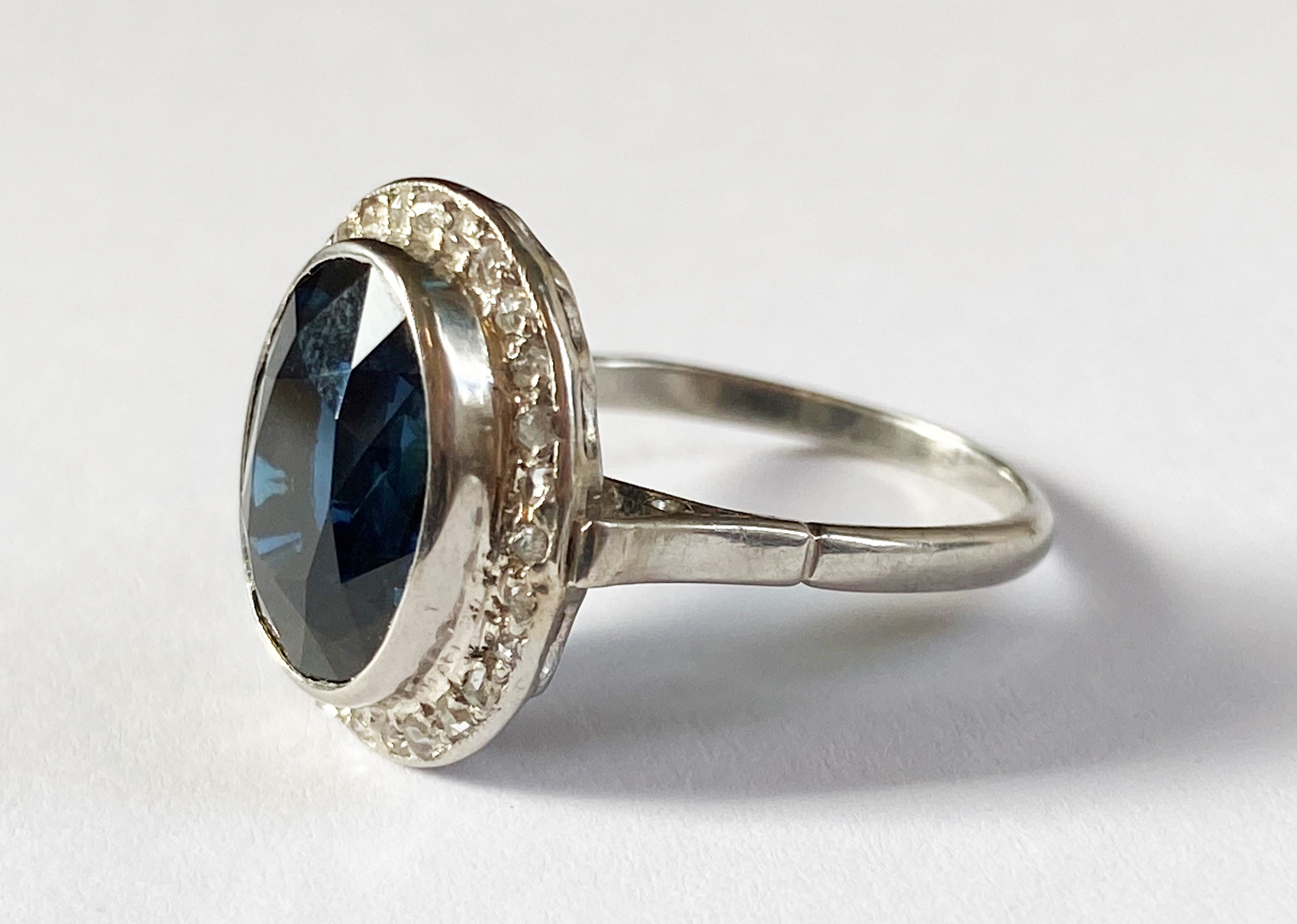 A sapphire and diamond cluster ring, the central oval mixed cut blue sapphire (measuring 12.20mm x - Image 4 of 7
