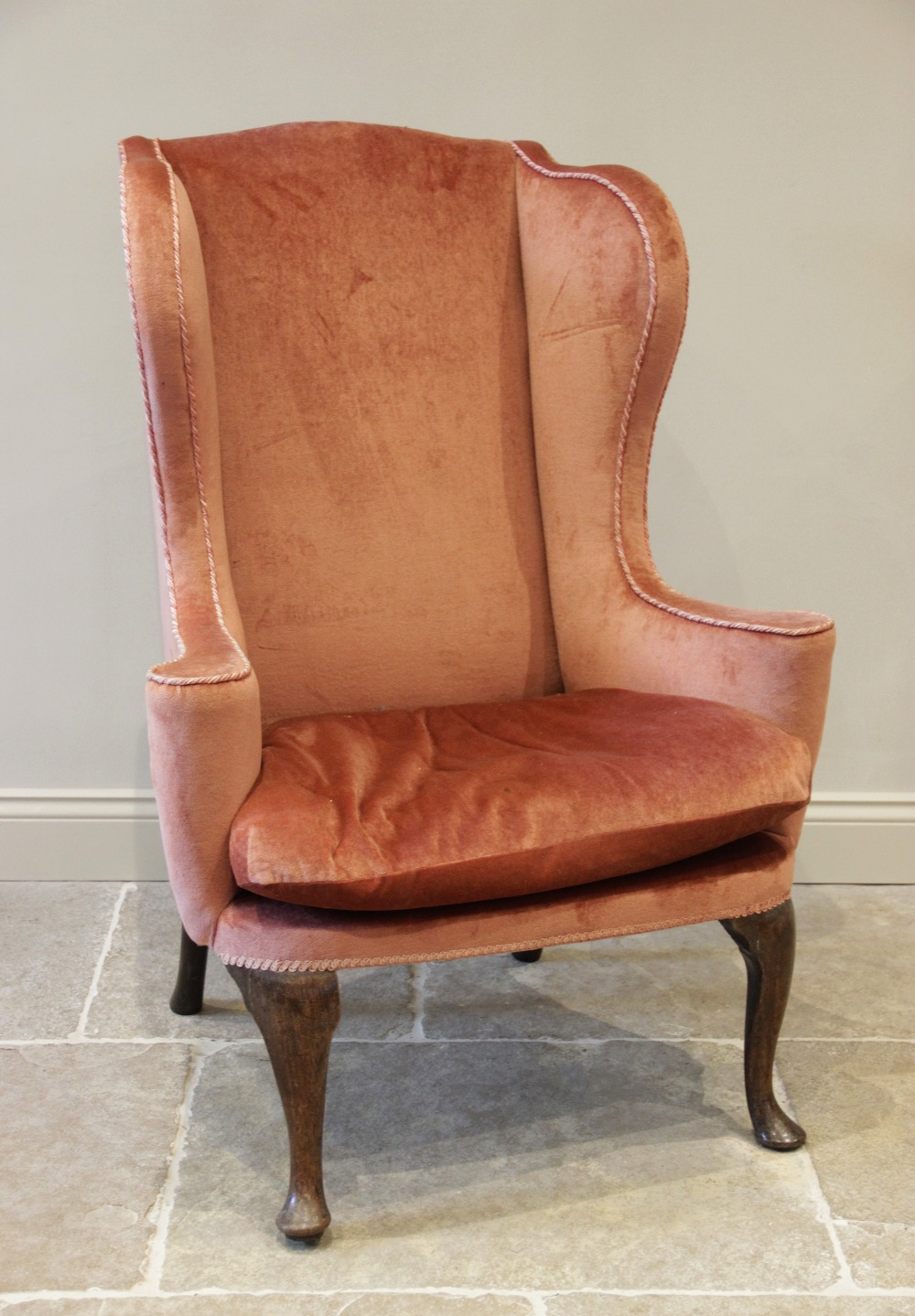 A George III wing back fireside armchair, later re-covered in pink velour with applied rope